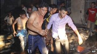 Rescuers rush victims of a bomb attack in Basra to hospital (7 August 2010)