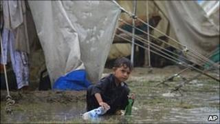 A child plays in the rain, Risalpur, Pakistan, 08/08
