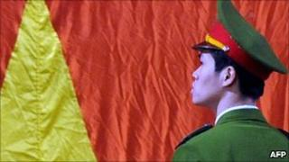 File image of a policeman in Hanoi standing in front of the Vietnamese flag
