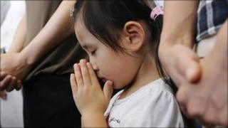 A girl offers a prayer during a ceremony to mark the 65th anniversary of the Nagasaki bomb attack