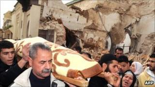 People carry a stretcher next to the collapsed minaret in Meknes (20 February 2010)