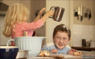 Sister tips flour over brother's head
