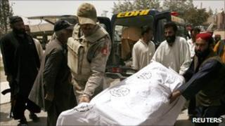 A Frontier Corp officer and rescue workers move the body of a victim killed by unidentified gunmen to a hospital in Quetta
