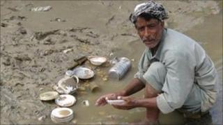Man washing dishes in flood water. Photo: Owais Barlas