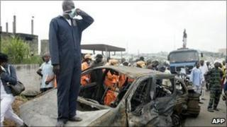 A rescue worker stands on one of the burnt vehicles at the scene of the accident on Lagos-Ibadan highway on 16 August 2010