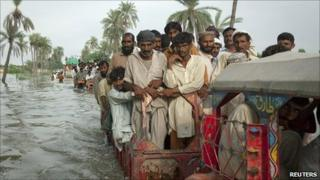 Villagers travel on tractors through floodwater in Punjab province, Pakistan (16 August 2010)