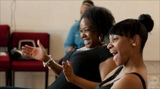 Two girls laugh during rehearsals at the Theatre Royal Stratford East