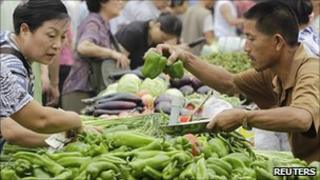 Customers select vegetables at a market in central Beijing