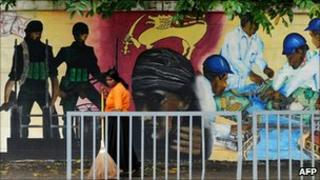 A Sri Lankan street cleaner sweeps the pavement alongside a mural in Colombo depicting the victory over Tamil Tiger rebels
