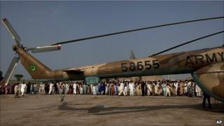 Pakistanis crowd around a helicopter after it delivered aid in Sindh Province, southern Pakistan, 20 August 2010