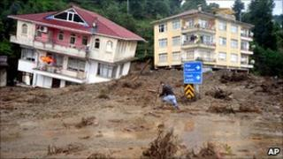 A man walks past a house tilted sideways after landslides and floods, Turkey, 27 August 2010