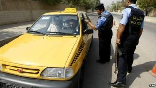 Iraqi police officers stop a taxi cab for a security check at a checkpoint in central Baghdad