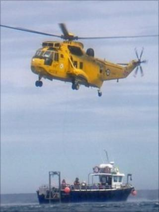 The RAF helicopter hovers over the boat