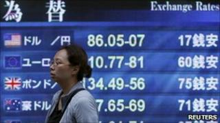 A woman walks past an electronic board displaying exchange rates at a business district in Tokyo