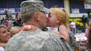 A child kisses her father, a soldier who recently returned home from Iraq