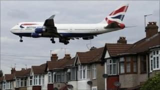 A plane flies over homes in west London