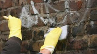 People washing graffiti in community payback scheme
