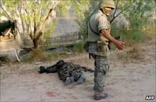 Mexican soldier standing next to dead body