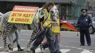 Russian police watch a horse painted to look like a zebra cross a road in Moscow