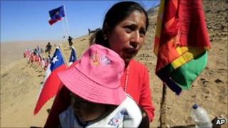 Monica Quispe, wife of trapped Bolivian miner Carlos Mamani, holds their baby next to a Bolivian flag outside the San Jose mine