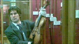 "Darryl Martin, curator of the University of Edinburgh's musical instrument collection, holding the ""Sherlock"" violin"