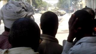 People watching a tank in a Mogadishu street