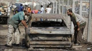 Men inspect a destroyed car after a bomb attack in Baghdad, 8 September