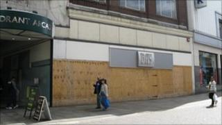 People walking past a boarded up shop