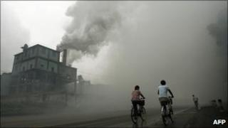Cyclists pass through thick pollution from a factory in Hebei province (2006)