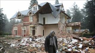 A woman walks past her ruined home near Christchurch