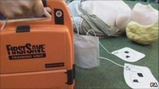 A defibrillator and a CPR Annie doll