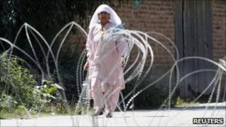 Woman walks past barbed wire in Srinagar (21 September 2010)