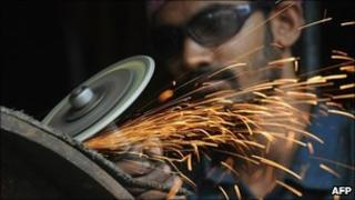 Indian labourer works at a metal workshop
