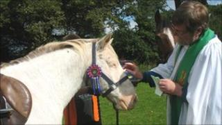 A horse called Chocolate receives a blessing from the Reverend Alan Jevons