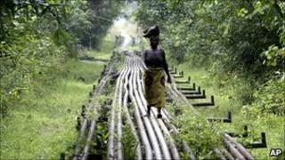 A woman walks along a pipe-line in Warri, Nigeria