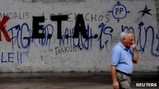 A man passes a wall bearing Eta graffiti in Mondragon, Spain, 6 September