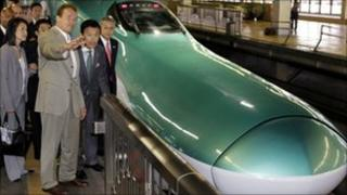 "Arnold Schwarzenegger and East Japan Railway's Vice President Masaki Ogata stand beside a ""shinkansen"" bullet train"