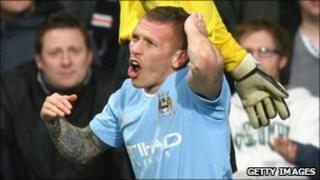 Craig Bellamy holds his head after being struck by coin