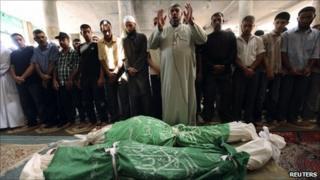 Palestinians pray near the bodies of Ibrahim and Husam Abu Saeed in Jabalya, northern Gaza Strip, 13 September