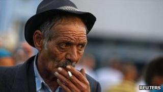 A deported Roma man smokes after arriving by air in Bucharest from Marseille, 14 September 2010