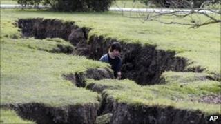 A man walks in a crack in the ground created by the earthquake, on 9 September 2010