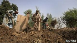Residents remove debris from their destroyed home in NW Pakistan