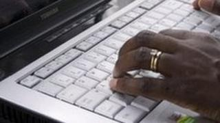 Man tapping on laptop keyboard