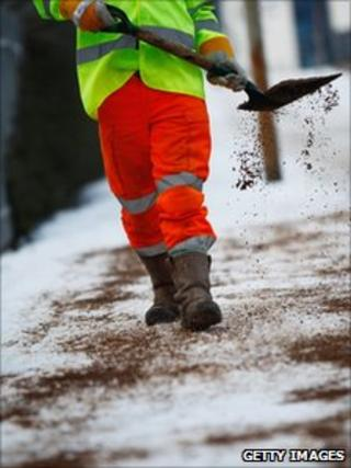 Council worker gritting a pavement
