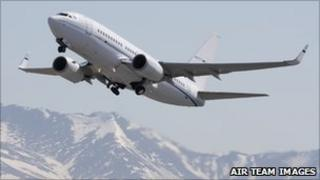 Boeing 737-700 in flight over mountains