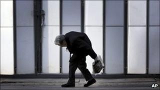 An elderly woman walks by a shrine in Tokyo