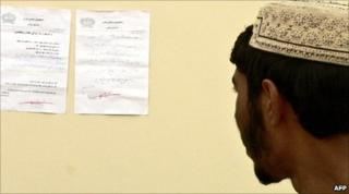 An Afghan man in Kandahar reads a letter posted on the wall by the Taliban, which warns people not to vote in the elections