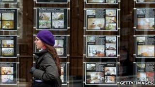 Woman walks past estate agent's window