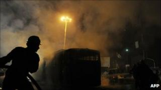 Pakistani firefighters extinguish a bus torched by mob