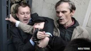 Gay rights campaigner Nikolai Alexeyev (left), clutching a puppet of Yuri Luzhkov, and a second protester resist arrest outside the Moscow mayor's office, 21 September
